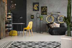 Black and yellow posters on concrete wall in spacious flat inter